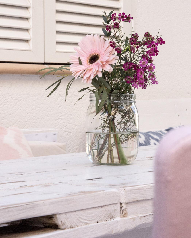 Rosane Gerberas und andere Blumen auf Cafétisch in Andratx